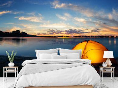 Orange tourist lit tent by the lake at sunset