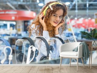 Red-haired girl standing at the counter in the store of electronic equipment choosing new headphones to buy. Listening to music in big headphones. Sales season at the Mall