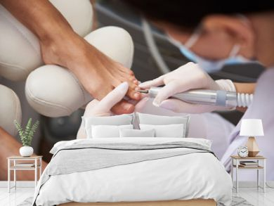 Pedicurist using electric nail drill while doing pedicure for young lady