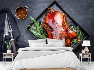 Traditional roasted stuffed Christmas Peking duck with herbs and sauce as top view on a rustic board