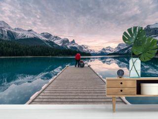 Couple traveler relaxing on wooden pier in Maligne lake at Spirit island, Jasper national park