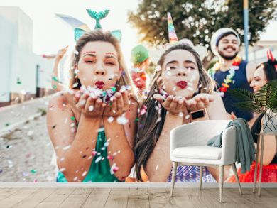 Brazilian Carnival. Young women in costume enjoying the carnival party blowing confetti