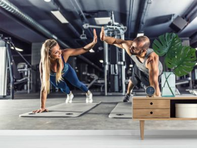 Sport couple doing plank exercise workout in fitness centrum. Man and woman practicing plank in the gym