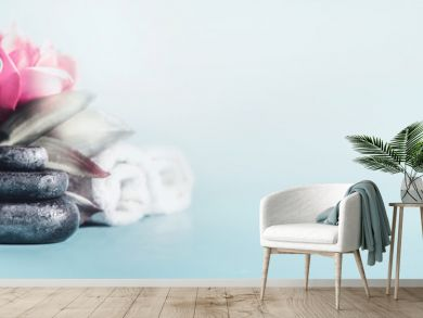 Spa and wellness concept with stack of zen stones, flowers and towels at light blue background with copy space. Relax and calm  treatment. Still life. Banner