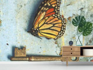 Vintage still life scene of a dead butterfly and old key on rustic aged blue paper and wood background. Unlocked hidden secrets, metamorphosis, freedom, nature and nostalgia concepts.
