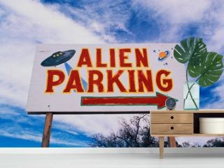 This is a road sign indicating where Alien Parking is. This is the original UFO crash site in Roswell. There are small UFOs on the sign with a large arrow pointing to the right.