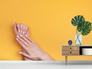 Beautiful female hands with a classic matte manicure on a yellow background. Place for your text.