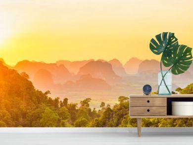 Beautiful panorama landscape with dramatic sunset, tropical rainforest and steep mountain ridge on horizon. Krabi, Thailand