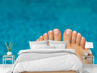 beautiful legs with french pedicure on the background of the pool