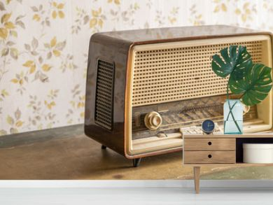 Old retro vintage radio on a aged wooden table illuminated by the sun