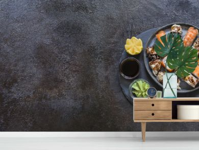 sushi rolls with rice and fish, soy sauce on a dark stone background