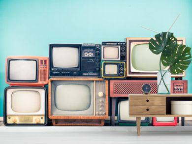 Retro classic TV receivers set from circa 60s, 70s and 80s, old wooden television stand with amplifier front mint blue wall background. Broadcasting, news concept. Vintage style filtered photo