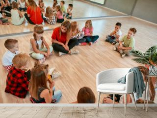 Analyzing mistakes. A group of little dancers sitting on the floor gathered around their female dance teacher and listening her carefully. Dance school