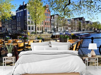Restaurant tables lining the beautiful canals of Amsterdam under blue skies during springtime, Netherlands