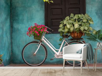 White vintage bike with basket full of flowers next to an old building in Danang, Vietnam