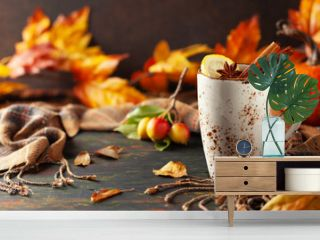 Autumn or winter spice tea in mug with seasonal fruits, berries, pumpkin and leaves on wooden table.