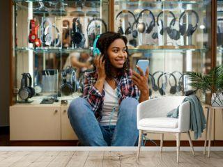 Happy buyer choosing headphones in audio store