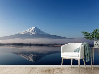 Beautiful scenery of snow capped Mount Fuji reflected in the peaceful lake water under blue clear sky with low stratus clouds at the foothill on a sunny winter morning at Kawaguchiko, Yamanashi, Japan