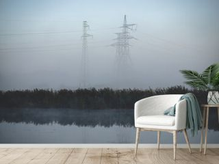 electric transit lines and pylons near river in misty morning in Latvia. Lots of dry reeds in october reflected in water. Autumn cold morning fog in background.