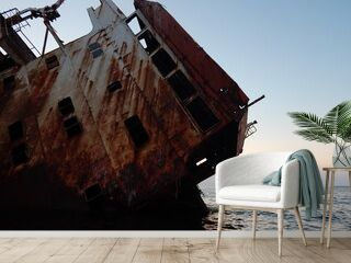 part of the sunken ship looks out of the water and is covered with rust