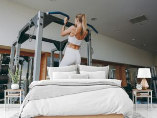 Back rear view young skinny strong sporty athletic sportswoman woman 20s wear white sportswear warm up training pulls up on horizontal bar on in gym indoors Workout sport motivation lifestyle concept.