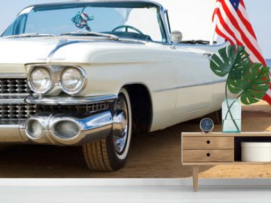 Classic white Cadillac at the beach with American flag
