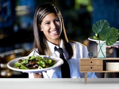 Hispanic waitress serving two plates of salad in a restaurant