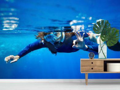 Scuba diver woman in  blue water.