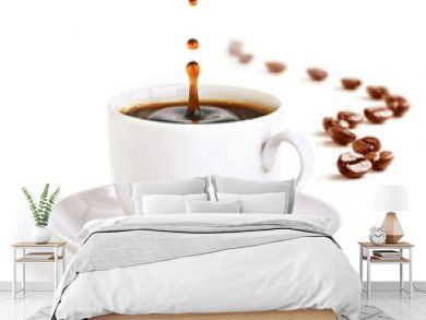 A cup of coffee with a splash of drops and coffee beans.