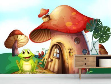 A green frog near a mushroom house