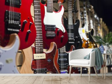 Many electric guitars hanging on wall in the shop.