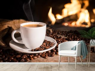Cup of hot coffee and coffee beans near fireplace