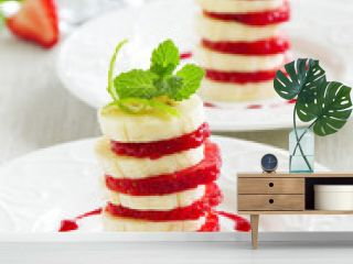 Dessert of strawberries and bananas with fruit sauce.