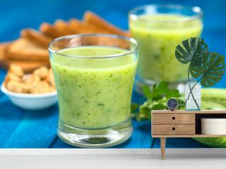 Zucchini cream soup served in glasses on blue wood