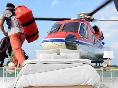 passenger carry his baggage to embark helicopter at oil rig plat
