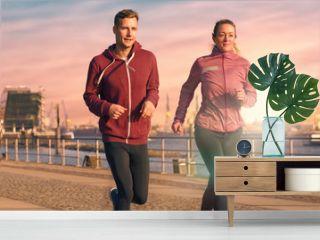 Aktives junges Paar beim Jogging an einer Uferpromenade