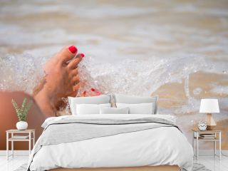 Tanned feet with pedicure  and the turquoise sea