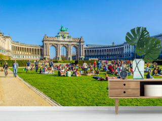 People are relaxing next to cinquantenaire monument in brussels during first sunny weekend in March.