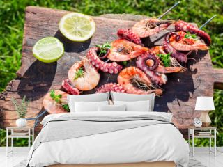 Tasty skewers of seafood with lemon and parsley in garden