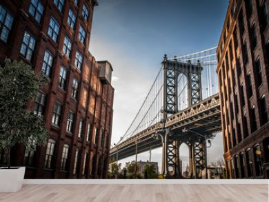 Manhattan bridge seen from a narrow alley enclosed by two brick buildings on a sunny day in summer
