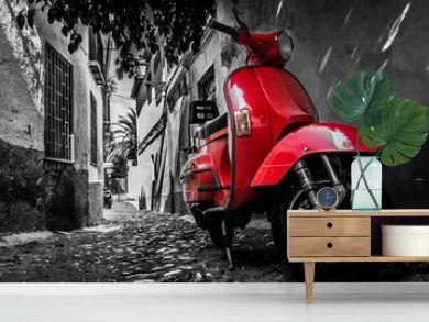 A red vespa scooter parked on a paved street