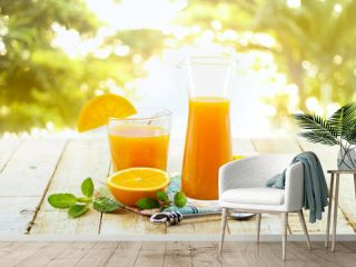 Glass and pitcher of orange juice on wooden, on green nature background