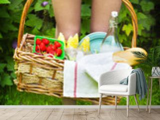 Young girl holding a picnic basket with berries, lemonade and br
