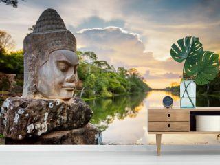 Stone face Asura and sunset over moat. Angkor Thom, Cambodia