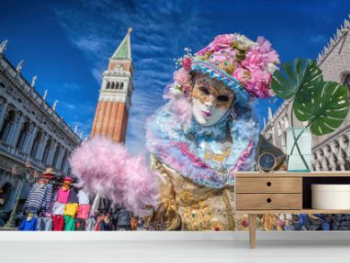 Carnival mask against bell tower on San Marco square in Venice