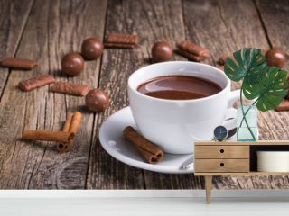 White cup of delicious hot chocolate with candies on table.