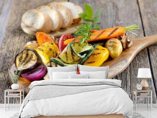 Vegan grillen: Gemischtes Gemüse vom Grill mit Kräutern, Gewürzen und Olivenöl, dazu frisches Ciabattabrot - Mixed grilled vegetables on a wooden cutting board served with Italian ciabatta bread