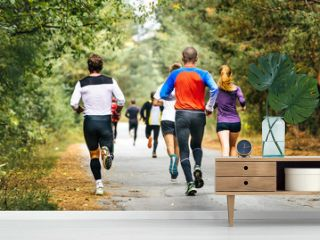 group of runners running down road in autumn Park with fallen yellow leaves. competition marathon