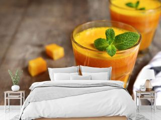 Two portions of fresh pumpkin juice with mint leaf in a glasses.