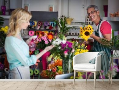 Smiling florist spraying water on flowers in flower shop